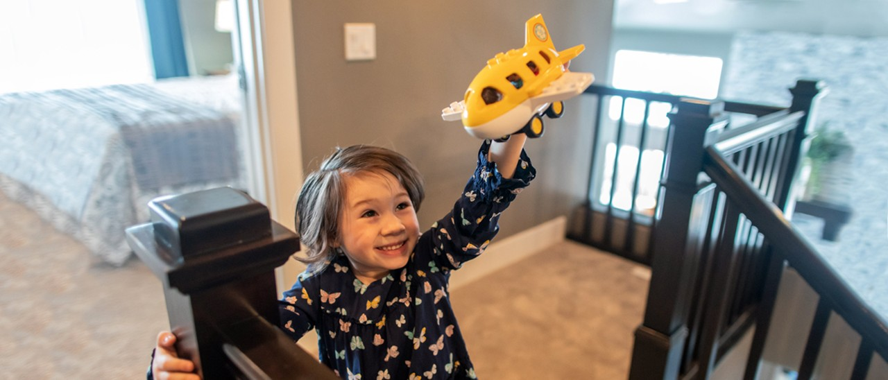 Girl Flying Toy Airplane in House
